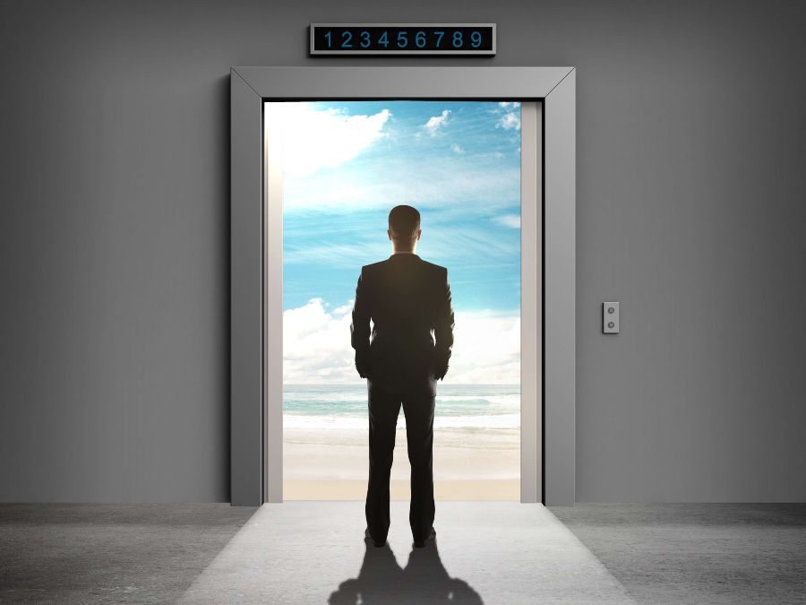 Businessman with hands in pocket looking out door to blue sky