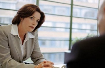 Brown-haired woman in business clothes talking to a male employee