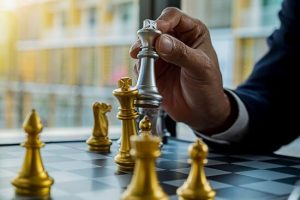 Business man holding silver chess piece